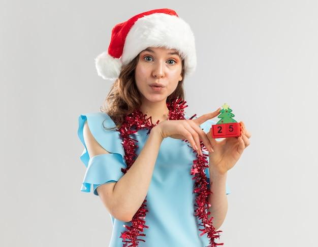 Junge frau in der blauen spitze und in der weihnachtsmannmütze mit lametta um ihren hals, der spielzeugwürfel mit weihnachtsdatum hält, das glücklich und fröhlich lächelnd schaut