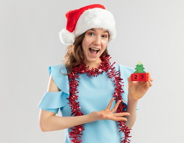 Junge frau in der blauen spitze und in der weihnachtsmannmütze mit lametta um ihren hals, der spielzeugwürfel mit weihnachtsdatum hält, das mit arm der hand glücklich und aufgeregt präsentiert