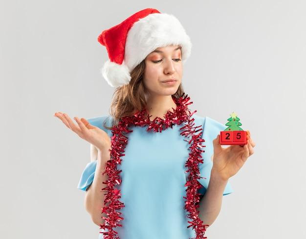 Junge frau in der blauen spitze und in der weihnachtsmannmütze mit lametta um ihren hals, der spielzeugwürfel mit weihnachtsdatum hält, das mit erhobenem arm zuversichtlich schaut