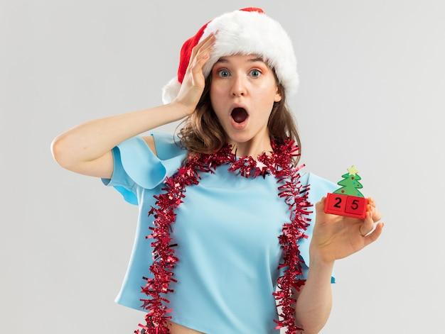 Junge frau in der blauen spitze und in der weihnachtsmannmütze mit lametta um ihren hals, der spielzeugwürfel mit weihnachtsdatum hält, das mit hand auf ihrem kopf erstaunt schaut