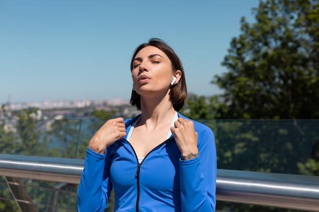 Junge frau in der blauen sportkleidung auf der brücke am heißen sonnigen morgen mit kabellosen kopfhörern, die sich mit den händen ausruhen, müde nach dem joggen des trainings