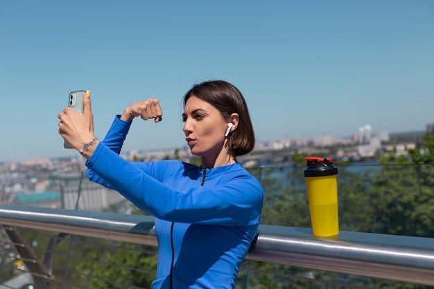 Junge frau in der blauen sportkleidung auf der brücke am heißen sonnigen morgen mit kabellosen kopfhörern und handy, nehmen selfie-foto-video für soziale netzwerke zeigt ihre muskeln bizeps