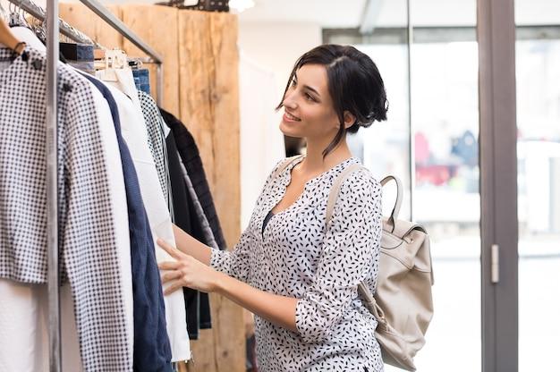 Junge frau in der boutique, die neue kleidung auswählt, um zu kaufen