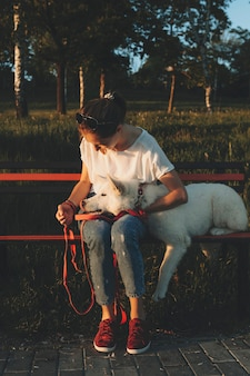 Junge frau in der freizeitkleidung, die bei sonnenuntergang auf hölzerner parkbank sitzt, die weißen hund umarmt und betrachtet, der kopf auf ihrem schoß legt