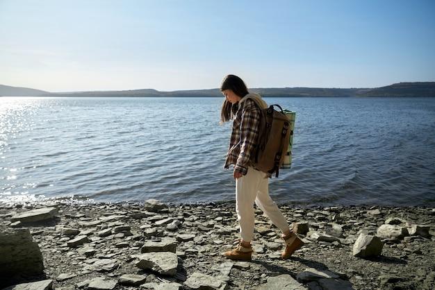 Junge frau in der freizeitkleidung, die entlang flussufer geht