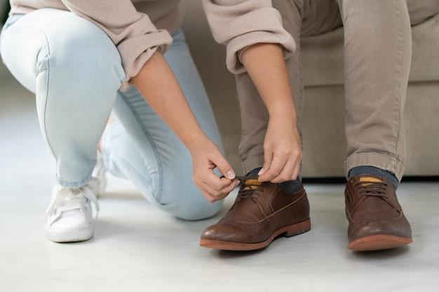 Junge frau in der freizeitkleidung, die ihrem kranken behinderten vater hilft, schnürsenkel auf braunen stiefeln zu hause zu binden