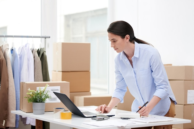 Junge frau in der freizeitkleidung, die laptopanzeige beim machen von notizen im notizblock beim arbeiten im online-shop-büro betrachtet