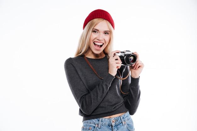 Junge frau in der freizeitkleidung stehend und hält retro-kamera
