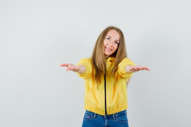 Junge frau in der gelben bomberjacke und in der blauen jeans, die einladen, zu kommen und optimistisch zu schauen
