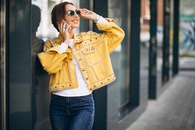 Junge frau in der gelben jacke unter verwendung des telefons draußen in der straße