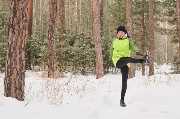 Junge frau in der grünen jacke, die im winterwald steht und bein beim training beiseite hebt