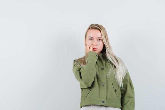 Junge frau in der grünen jacke, jeans, die auf kamera, vorderansicht fokussiert.