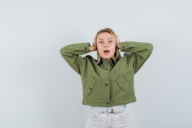 Junge frau in der grünen jacke, jeans, die hände am ohr halten und stressig, vorderansicht schauen.