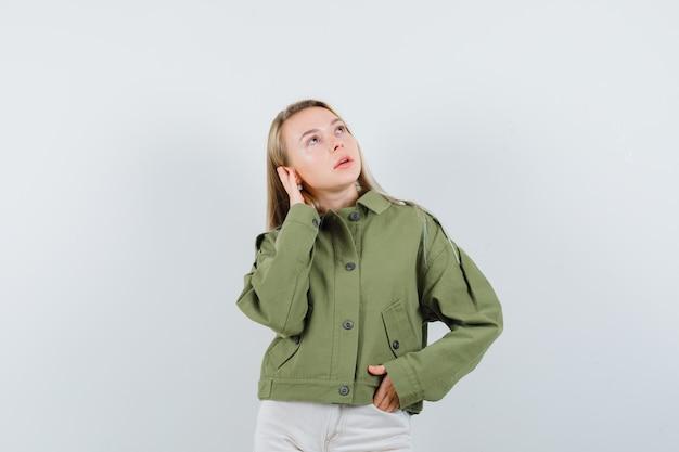 Junge frau in der grünen jacke, jeans posiert mit der hand am ohr und sieht beeindruckend aus, vorderansicht.