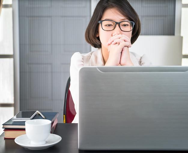 Junge frau in der intelligenten freizeitkleidung, die an laptop arbeitet