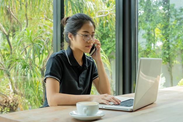 Junge frau in der kaffeestube unter verwendung eines laptops und unterhaltung an einem handy.