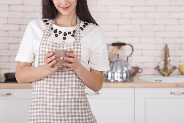 Junge frau in der küche. hausfrau in der küche stehen. frauen kochen.