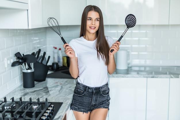 Junge frau in der küche. in den händen halten werkzeuge zum kochen von lebensmitteln.