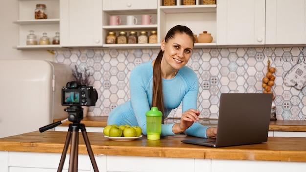 Junge frau in der küche mit lächelndem laptop. food blogger konzept. eine frau nimmt ein video über gesunde ernährung auf. kamera auf einem stativ.