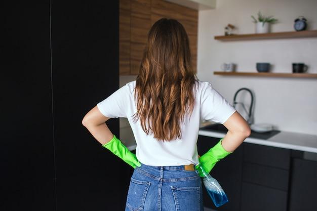 Junge frau in der küche. rückansicht ob brünette tragen grüne schutzhandschuhe zur reinigung. halten sie das tuch in der hand. bereit, die küche zu reinigen.