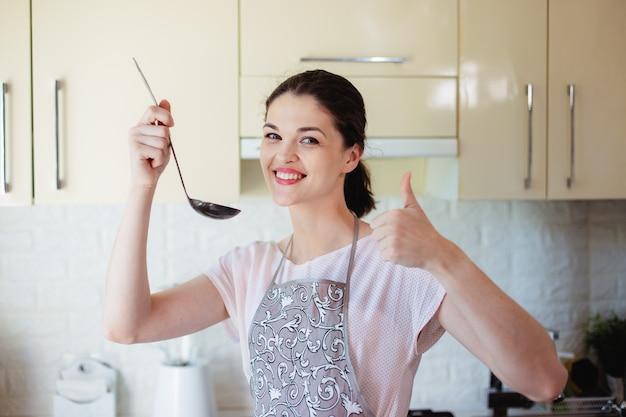 Junge frau in der küche schmeckt suppe auf salz mit einer kelle. daumen zeigen