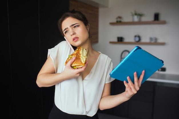 Junge frau in der küche während der quarantäne. mädchen, das am telefon spricht und sandwich isst. geschäftsfrau halten blaue tablette in der hand. heimbüro und fernarbeit. kommunikation und online-konversation.