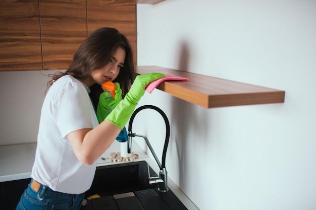Junge frau in der küche während der quarantäne. mädchen, das regaloberfläche sorgfältig reinigt. mit einem tuch und reinigungsspray. tragen sie grüne handschuhe um die hände.