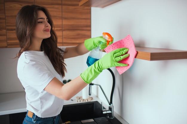 Junge frau in der küche während der quarantäne. mädchen, das spray zum reinigen von regalen von staub verwendet. haushalt und pflege. attraktives positives mädchenlächeln.