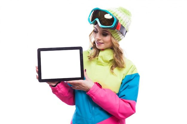 Junge frau in der leeren tablette des skianzuggriffs