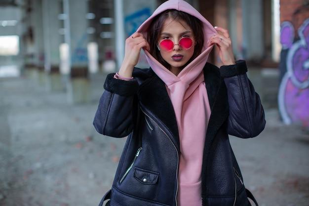 Junge frau in der lila brille, die eine rosa kapuze trägt