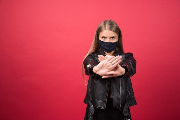 Junge frau in der medizinischen maske, die steht und hände kreuzt, die negatives vorzeichen der ablehnung tun