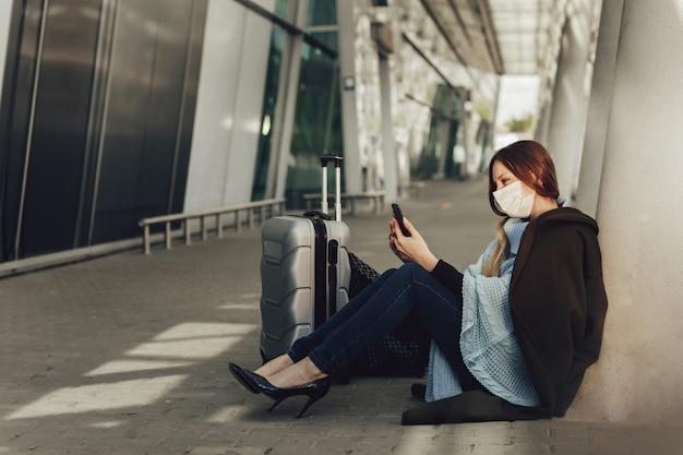 Junge frau in der medizinischen maske sitzt nahe gepäck im flughafen. frau, die auf flug wartet, ein handy benutzt und kamera betrachtet.