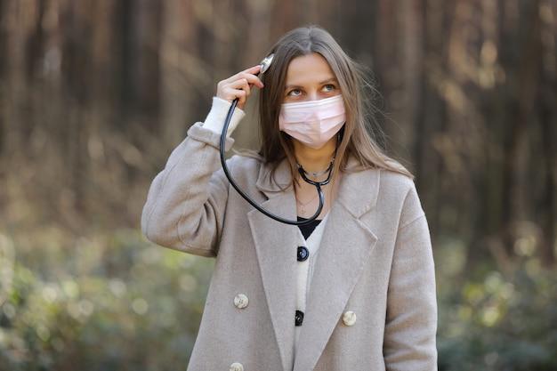 Junge frau in der medizinischen schutzmaske, die stethoskop hält und ihren kopf hört. medizinische versorgung. selektiver fokus. covid 19 ncov coronavirus-krankheit