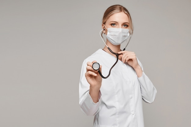 Junge frau in der medizinischen uniform und in der schutzmaske benutzt ein stethoskop und posiert am grauen hintergrund, isoliert. gesundheitssystem und notfallkonzept
