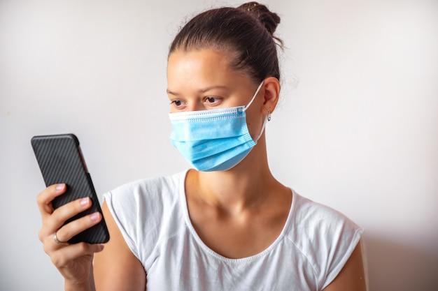 Junge frau in der medizinmaske mit smartphone in der hand auf dem weißen hintergrund, medizinisches konzept