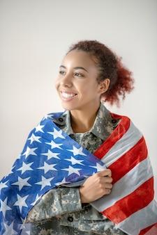 Junge frau in der militäruniform, die die amerikanische flagge hält