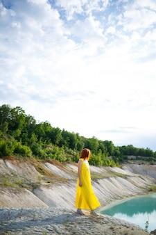 Junge frau in der nähe eines sees mit azurblauem wasser und steinigen bergen mit grünen bäumen. schöne aussicht auf den see im wald