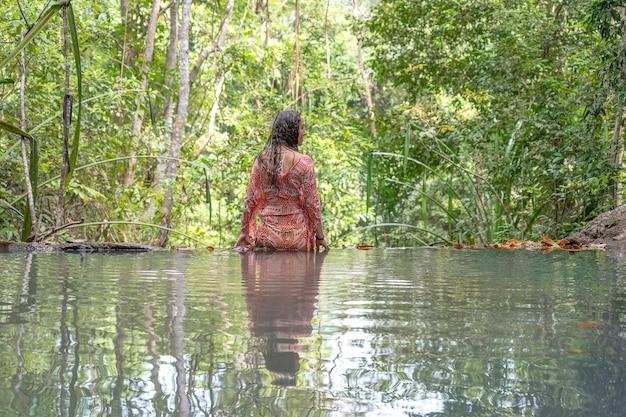 Junge frau in der nähe von türkisfarbenem wasser des wasserfalls im tiefen tropischen regenwald, insel koh phangan, thailand