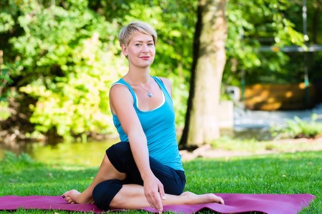 Junge frau in der natur, die yoga tut