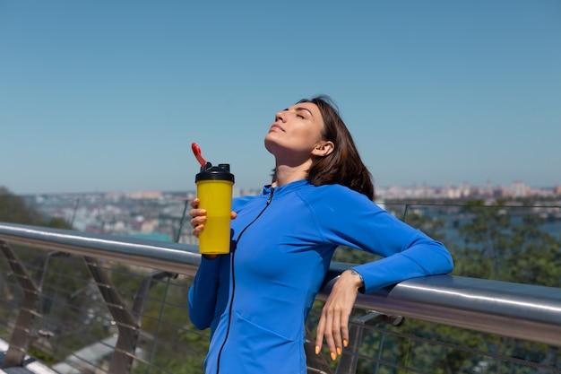 Junge frau in der passenden sportkleidung auf brücke am heißen sonnigen morgen mit flasche wasserschüttler durstig nach dem training müde trinken