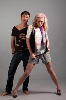 Junge frau in der rosa kleidung, die jungen mann in schwarz von hinten über gey hintergrund im fotostudio umarmt. beauty- und fashion-lifestyle-konzept