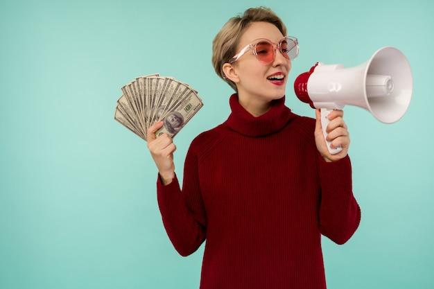 Junge frau in der rosa sonnenbrille mit dem geld, das zum lautsprecher schreit