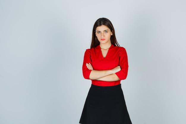 Junge frau in der roten bluse, im schwarzen rock stehende arme verschränkt und selbstbewusst aussehend