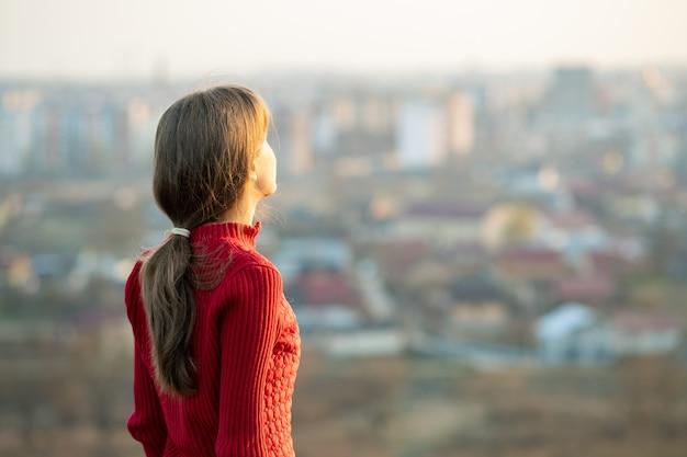 Junge frau in der roten jacke, die draußen steht und abendansicht genießt. entspannungs-, freiheits- und wellnesskonzept.