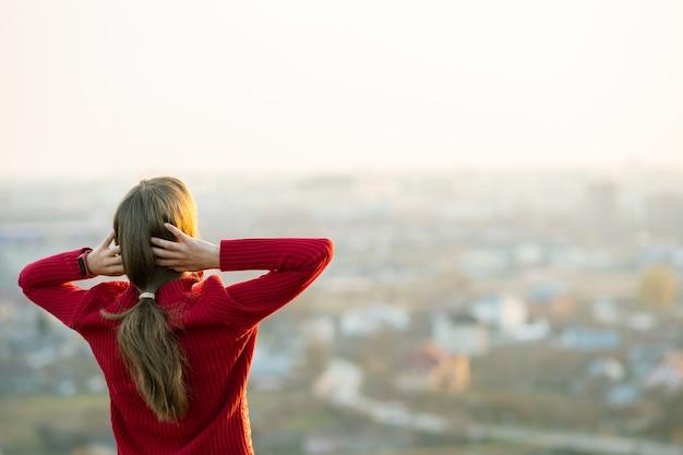 Junge frau in der roten jacke, die mit ihren händen hinter dem kopf draußen steht und abendblick genießt. entspannungs-, freiheits- und wellnesskonzept.