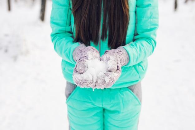 Junge frau in der schneeberglandschaft, die weißen schnee in ihren händen hält, um einen schneeball zu machen
