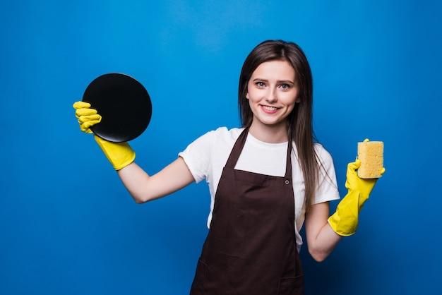 Junge frau in der schürze mit schwamm, der gewaschenes gericht betrachtet. sauberes geschirr, ordnung im haus ist viel arbeit. perfekte hausfrau verdient rang