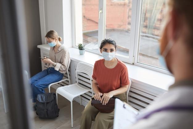 Junge frau in der schutzmaske, die in der warteschlange im krankenhaus sitzt, während arzt sie trifft