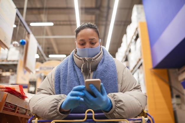 Junge frau in der schutzmaske und in den handschuhen, die eine nachricht auf handy während des stehens mit einkaufswagen im supermarkt tippen