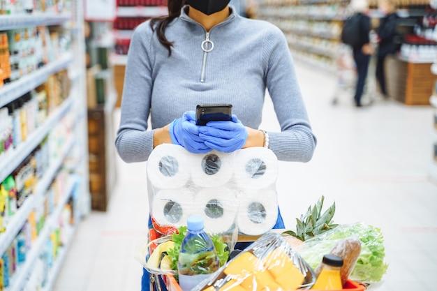 Junge frau in der schutzmaske und in den handschuhen, die einen barcode scannen